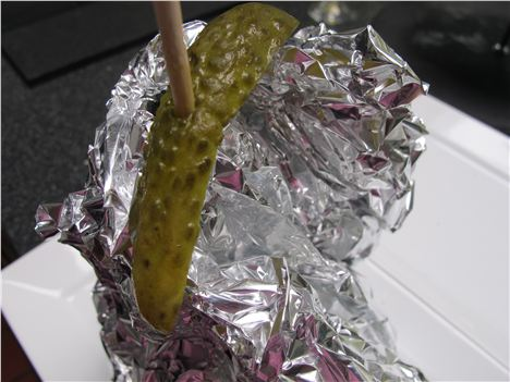 Pleasantly folded burger for take-out with gherkin atop